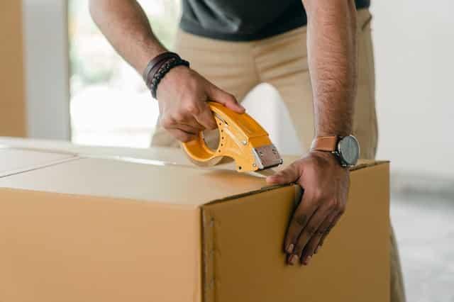 Man taping moving box.